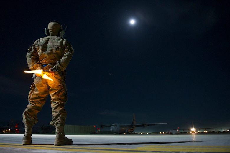 Senior Airman Alec Flores, a 455th Expeditionary Aircraft Maintenance Squadron crew chief, prepares to guide a C-130J Super Hercules onto a taxiway as it leaves on a night sortie at Bagram Airfield, Afghanistan, Feb. 22, 2016. The 455th EAMXS ensures that aircraft at Bagram Airfield are prepared for flight and return them to a mission-ready state once they land. (U.S. Air Force photo/Tech Sgt. Robert Cloys)