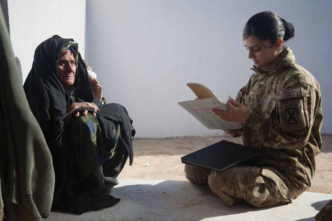 A U.S. Army Sergeant writes down information from a local woman at the Woman's Center near the