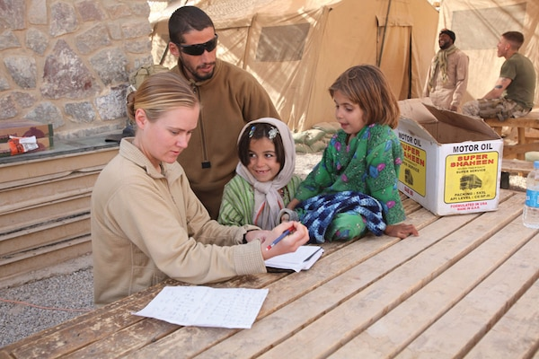 A U.S. Army Staff Sergeant, with the aid of an interpreter, helps two local Afghan girls practice reading and spelling.