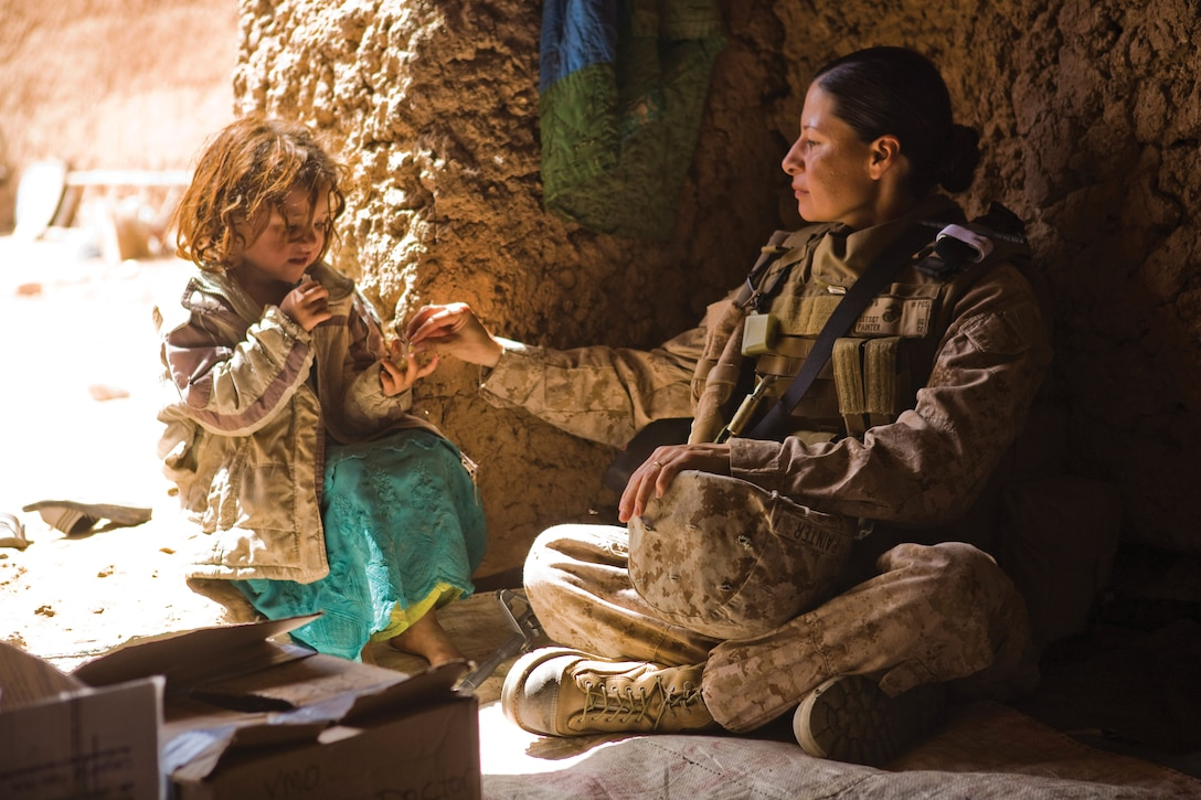 Member of a U.S. Marine Corps Female Engagement Team watches over an Afghan girl while the girl's mother receives medical attention from another team member.