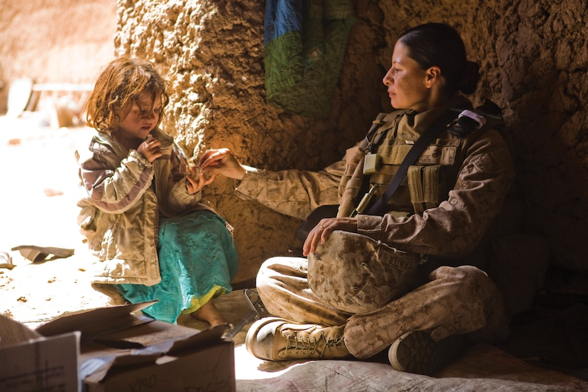 Member of a U.S. Marine Corps Female Engagement Team watches over an Afghan girl while the girl's