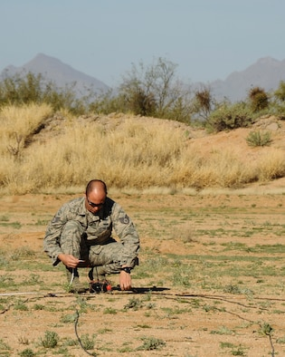 U.S. Air Force Staff Sgt. Patrick Barbarino, 355th Civil Engineer Squadron explosive ordnance disposal technician, prepares the firing point for a simulated bombing run detonation at Davis-Monthan Air Force Base, Ariz., Feb. 18, 2016. The EOD flight practiced for the demonstration they will display at the upcoming 2016 Thunder and Lighting over Arizona open house.  (U.S. Air Force photo by Airman 1st Class Mya M. Crosby/Released)
