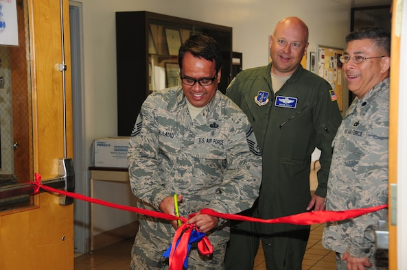 Senior Master Sgt. Neil Bulatao cuts the ribbon for the official re-opening of the 146th Airlift Wing's dining facility alongside Vice Wing Commander Col. Brian Kelly (center) and Force Support Squadron Commander Lt. Col. Abe Quinteros (right). The DFAC has new flooring, furniture and flat screen TVs which all went in after February drill. (U.S. Air National Guard photo by Senior Amn.. Madeleine Richards/Released)
