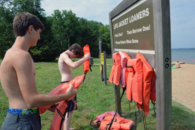"""Two young swimmers place life vests from the Life Jacket Loaner board at the Cheatham Dam beach area in Ashland City, Tennessee. Every year thousands of people in the United States mourn the loss of loved ones who could have survived if they had been wearing a life jacket while spending time on or near our nation's waters. To heighten awareness, the U.S. Army Corps of Engineers recently launched a national water safety campaign titled """"Life Jackets Worn - Nobody Mourns."""