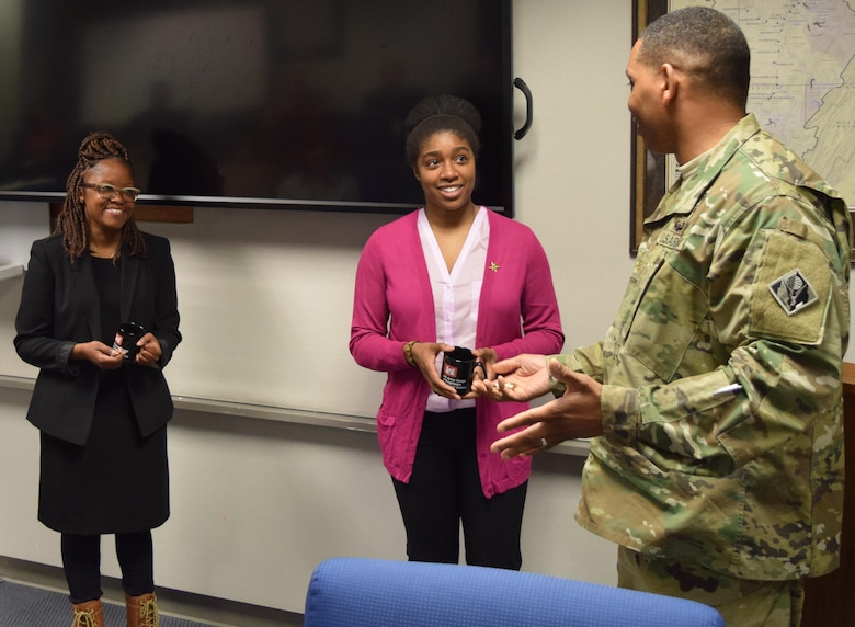 Riedolia Moore-Ellis, National Society of Black Engineers Pittsburgh Professionals Chapter president, and Lachelle Binion from the Pittsburgh Urban League, received district cups and commander's coins from Maj. Cornelius Batts, district deputy commander, after their Black History Month presentation, Feb. 25 at the Federal Building in Pittsburgh.