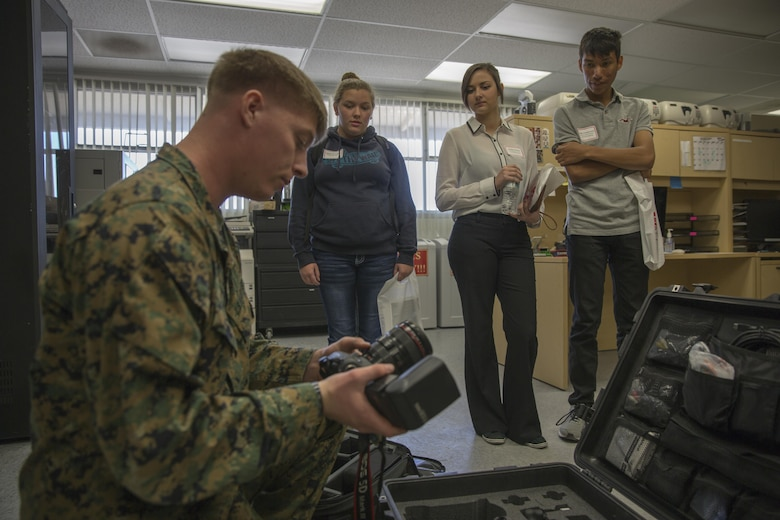 Lance Cpl. Eric Clayton, combat photographer, Headquarters Battalion, mentors Twentynine Palms High School students who have an interest in becoming photographers during the 13th annual Job Shadowing Event aboard the Combat Center Feb. 23, 2016. The event began as a partnership between the Morongo Unified School District and the installation and provides students with insight on potential careers. (Official Marine Corps photo by Lance Cpl. Levi Schultz/Released)