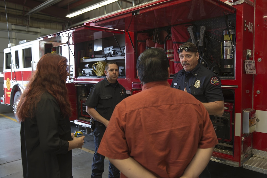 Anthony Marchisio and Wes Collins, fire inspection protectors, Combat Center Fire Department, show Twentynine Palms High School Students their firefighting equipment during the 13th annual Job Shadowing Event aboard the Combat Center Feb. 23, 2016. The event began as a partnership between the Morongo Unified School District and the installation and provides students with insight on potential careers. (Official Marine Corps photo by Lance Cpl. Levi Schultz/Released)