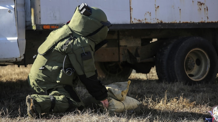 A Marine with  Explosive Ordnance Disposal Platoon, Combat Logistics Battalion 2, places a sandbag during a field exercise at Marine Corps Base Camp Lejeune, N.C., March 2, 2016. Marines used equipment such as compact metal detectors, bomb suits and a TALON robot to locate and handle ordnance, which took the form of a simulated IED, ammunition or artillery shell.