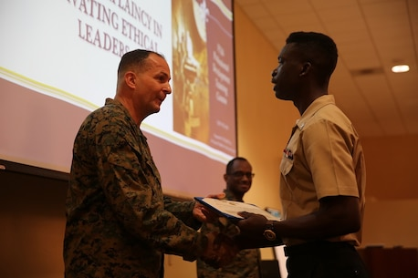 Maj. Gen. Daniel J. O'Donohue presents the Naval Chaplaincy Excellence award to Petty Officer 3rd Class Dawaylon Farr at Camp Pendleton, Feb. 23, 2016. The ceremony recognized Lt. Michael Kennedy and Petty Officer 3rd Class Dawaylon Farr for going above and beyond the call of duty to provide spiritual guidance and renewed faith to Marines and sailors serving I Marine Expeditionary Force. O'Donohue, the commanding general of 1st Marine Division, was a guest speaker and presented awards to the recipients.  Kennedy is a chaplain with 1st Battalion, 1st Marine Regiment, 1st Mar. Div. Farr is a religious program specialist with 1st Bn., 4th Marines. (U.S. Marine Corps photo by Pvt. Robert Bliss/Released)