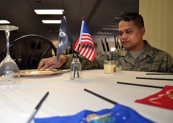 Air Force Senior Airman Alan Phe of the Pennsylvania Air National Guard's 111th Force Support Squadron Service Flight on Horsham Air Guard Station, Pa., removes the lemon slice from the bread plate of the prisoners of war/missing in action table he created recently at the station's dining facility, Feb. 22, 2016. U.S. Air Force photo by Tech. Sgt. Andria Allmond