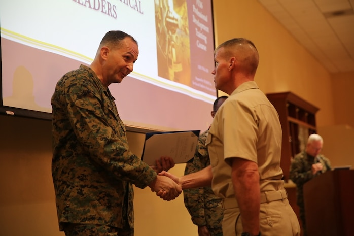 Maj. Gen. Daniel J. O'Donohue presents the Naval Chaplaincy Excellence award to Lt. Michael Kennedy at Camp Pendleton, Feb. 23, 2016. The ceremony recognized Lt. Michael Kennedy and Petty Officer 3rd Class Dawaylon Farr for going above and beyond the call of duty to provide spiritual guidance and renewed faith to Marines and sailors serving I Marine Expeditionary Force. O'Donohue is the commanding general of 1st Marine Division.  Kennedy is a chaplain with 1st Battalion, 1st Marine Regiment, 1st Mar. Div. Farr is a religious program specialist with 1st Bn., 4th Marines. (U.S. Marine Corps photo by Pvt. Robert Bliss/Released)