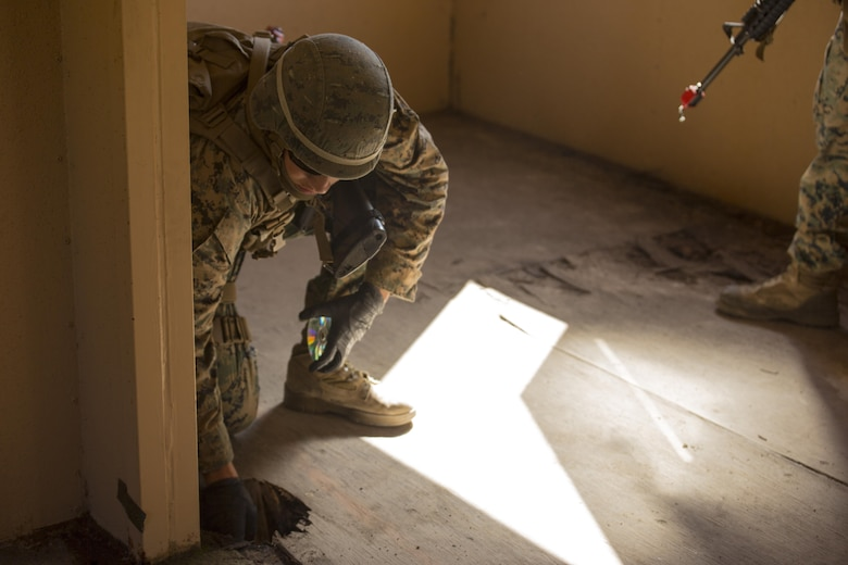 A Marine with 2nd Law Enforcement Battalion locates a DVD during Tactical Site Exploitation training at Camp Lejeune, N.C., March 3, 2016. After raiding the building, the Marines thoroughly searched the area using forensics technology to discover evidence that can help identify who owned the material. (U.S. Marine Corps photo by Lance Cpl. Samuel Guerra/Released)