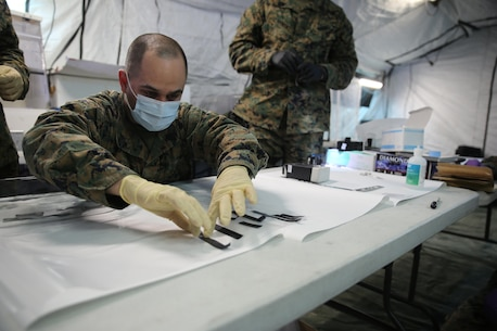 Sgt. Alberto Camacho, military policeman for Charlie Company, 2nd Law Enforcement Battalion, separates evidence without fingerprints during Tactical Site Exploitation training at Camp Lejeune, N.C., March 3, 2016. The training emphasizes the importance of leaving the evidence in pristine condition to ensure they get the most accurate intelligence necessary to identify the enemies. (U.S. Marine Corps photo by Lance Cpl. Samuel Guerra/Released)