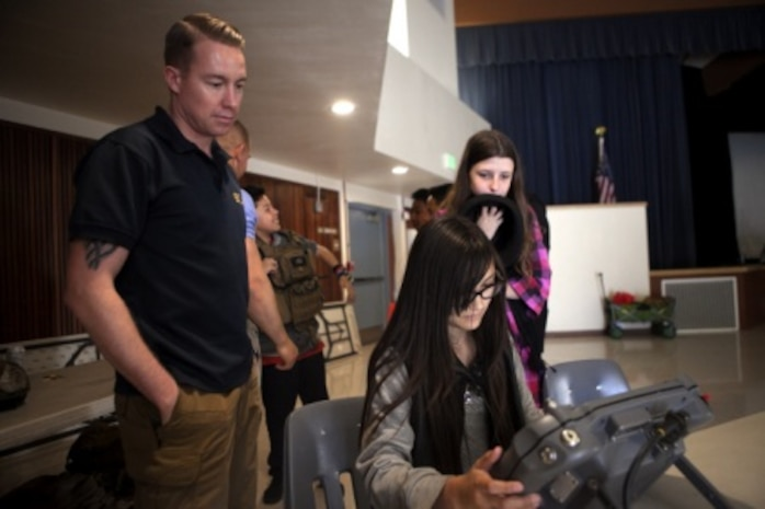 Sergeant Craig Matz, an Explosive Ordnance Disposal technician with 1st EOD Company, 7th Engineer Support Battalion, 1st Marine Logistics Group, supervises a James E. Potter Junior High School student attempting to drive the ANDORS EOD robot during a visit to the school in Fallbrook, Calif., Feb. 29, 2016. During the visit, EOD Marines explained the various capabilities of military robots and performed a practical application of EOD's bomb-detecting robots.