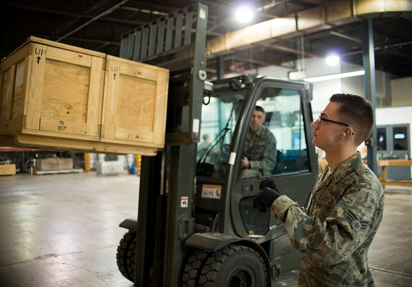 Senior Airman Kyle Metz, 30th Aerial Port Squadron, signals to a forklift operator on Feb. 7, 2016 at the Niagara Falls Air Reserve Station, N.Y. Metz was selected as the 914th Airlift Wing Spotlight performer for February 2016. (U.S. Air Force photo by Tech. Sgt. Stephanie Sawyer)