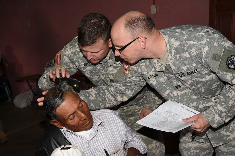 LA PAZ, Honduras – U.S. Army Capt. Michael Eaton (right front) and Sgt. Matthew Dickson (back), Joint Task Force-Bravo Medical Element providers, examine a Honduran patient with skin problems on the left side of his head during a Medical Readiness Training Exercise in La Paz Department, Honduras, March 2, 2016. Basic medical attention is one among many services provided during these exercises, where patients receive care that is otherwise unavailable in their communities from Honduran and U.S. medical providers. (U.S. Army photo by Martin Chahin/Released)