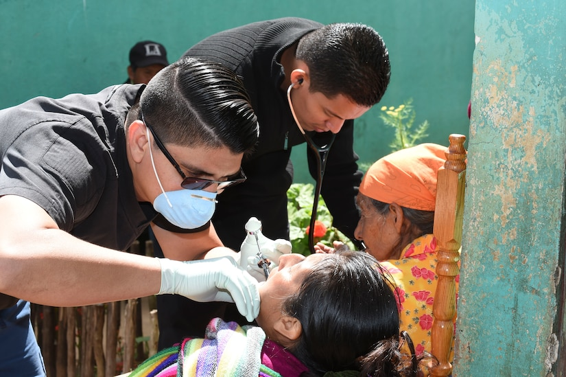 LA PAZ, Honduras – Honduran physicians, Dr. Jose Elias Dubón (front) and Dr. Oscar Quezada (back) provide dental and medical services to two patients during a Medical Readiness Training Exercise in La Paz Department, Honduras, March 2, 2016. During the two-day exercise patients received basic dental and medical treatment, as well as an initial health class where they were given vitamins and deworming medication. (U.S. Army photo by Martin Chahin/Released)