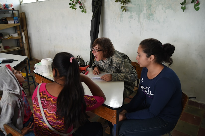 LA PAZ, Honduras – U.S. Army Capt. Michelle Russ, Joint Task Force-Bravo Medical Element medical provider examines a child during a Medical Readiness Training Exercise in La Paz Department, Honduras, March 2, 2016.  Honduran volunteers served as translators, helping U.S. Servicemembers communicate with the patients when needed. A total of 643 Honduran patients were seen during the two-day MEDRETE. (U.S. Army photo by Martin Chahin/Released).