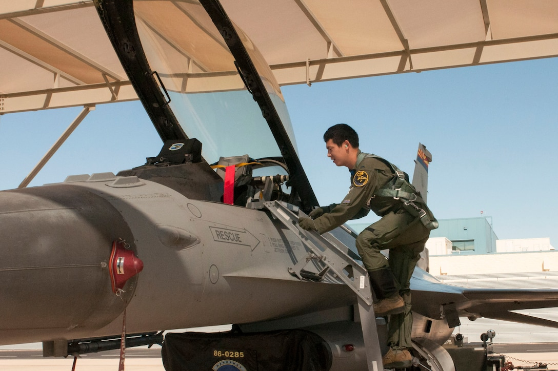 """1st Lt. Toshiaki Kawanishi climbs up into the cockpit of an F-16 Fighting Falcon during his pilot training at the Arizona Air National Guard's 162nd Wing located at Tucson International Airport. """"We cannot accomplish the mission with only one country,"""" said Kawanishi. """"This is a good opportunity to learn about other nationalities and personalities, and to be able to apply that to the mission in the future."""" (U.S. Air National Guard photo by 2nd Lt. Lacey Roberts)"""