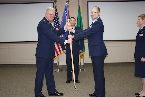 Col. William Krueger, 225th Air Defense Group commander, hands off the guidon to Lt. Col. Brett Bosselmann, 225th Air Defense Squadron commander, during the 225th Air Defense Squadron change of command at the Western Air Defense Sector at Joint Base Lewis-McChord, Wash., Jan. 29, 2016. The 225th ADG is a subordinate unit of the 225th Air Defense Group, which conducts the Western Air Defense Sector's (WADS) mission. WADS is responsible for air sovereignty and counter-air operations over the western United States and directs a variety of assets to defend 2.2 million square miles of land and sea. (U.S. Air National Guard photo by 1st Lt. Colette Muller/Released)