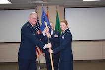 Col. William Krueger, 225th Air Defense Group commander, hands off the guidon to Col. Paige Abbott, 225th Support Squadron commander, during the 225th Support Squadron change of command at the Western Air Defense Sector on Joint Base Lewis-McChord, Wash., Jan. 29, 2016. The 225th Support Squadron is a subordinate unit of the 225th Air Defense Group, which conducts the Western Air Defense Sector's (WADS) mission. WADS is responsible for air sovereignty and counter-air operations over the western United States and directs a variety of assets to defend 2.2 million square miles of land and sea. (U.S. Air National Guard photo by 1st Lt. Colette Muller/Released)