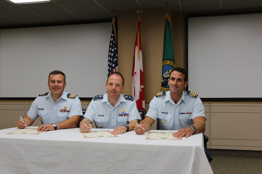 Canadian Brig. Gen. Alain Pelletier (center), deputy commander Continental U.S. North American Aerospace Defense Region-First Air Force (CONR-1AF), presides over the Canadian Detachment Joint Base Lewis-McChord change of command.  Lt. Col. Matthew Wappler (left) assumes command from the outgoing commander, Lt. Col. Mark Roberts (right), during the ceremonial signing of the change of command scrolls.   The ceremony took place July 8 at the Western Air Defense Sector, Joint Base Lewis-McChord, Wash.