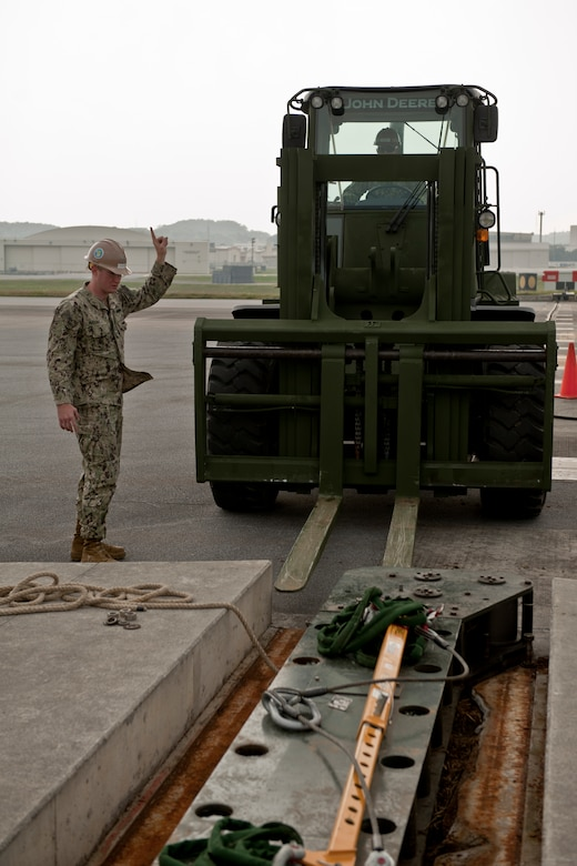 U.S. Navy Equipment Operator 2nd Class Joshua McDonald, Naval Mobile Construction Battalion 3 Seabees construction man, directs a forklift towards a fairlead beam on the flight line Feb. 29, 2016, at Kadena Air Base, Japan. Seabees utilized various heavy construction equipment to extract and replace an aircraft arresting barrier system. (U.S. Air Force photo by Senior Airman Peter Reft)