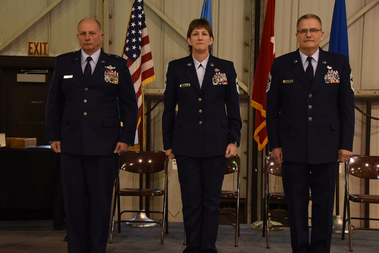 Brig. Gen. Matthew P. Jamison, Assistant Adjutant General for South Dakota Air National Guard, and retiring State Command Chief Master Sgt. James Welch stand at attention with incoming State Command Chief Master Sgt. Jean Gacke at Joe Foss Field, S.D. March 5, 2016. A ceremony was held to recognize the change of responsibility for these individuals. (U.S. Air National Guard photo by Staff Sgt. Luke Olson/Released)