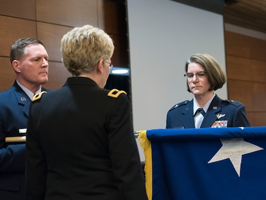 JOINT BASE ELMENDORF-RICHARDSON, Alaska -- Chief Master Sgt. Steven Calvin, the state command chief for the Alaska Air National Guard, unfurls the general's flag for new Brig. Gen. Karen Mansfield (right), commander of the Alaska Air National Guard, in a promotion ceremony at the Arctic Warrior Events Center here March 6, 2016. Mansfield became the third female general officer in the history of the Alaska Air National Guard. National Guard photo by Capt. John Callahan.