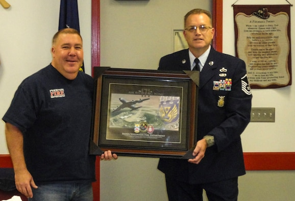 Master Sgt. Gary L. Shannon, 171st Installation Fire Chief, presents an appreciation award to Dave Trzciankia , Fire Chief of the Baden Volunteer Fire Department, Dec. 3, 2015. (U.S. Air National Guard Photo)