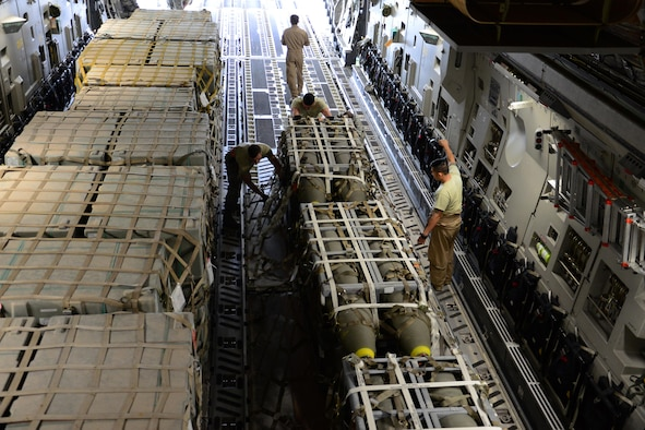 Airmen from the 8th Expeditionary Air Mobility Squadron Ramp Services team load munitions onto a C-17 Globemaster III at Al Udeid Air Base, Qatar, Feb. 26, 2016, in support of Operation Inherent Resolve. In February, the team loaded more than 3,500 tons of cargo onto U.S. aircraft. (U.S. Air Force photo/Tech. Sgt. James Hodgman)