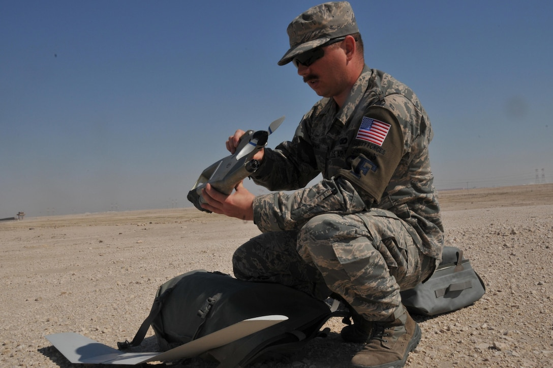 Senior Airman James McGaha, 379th Expeditionary Security Force Squadron patrolman, puts together a Raven B Digital Data Link drone, a small unmanned aircraft or drone, Feb. 19 at Al Udeid Air Base, Qatar. McGaha is a member of a two person team who operate the Raven B drone at AUAB. He is deployed from Yokota Air Base, Japan, and has been a patrolman for three years. (U.S. Air Force photo by Tech. Sgt. Terrica Y. Jones/Released)