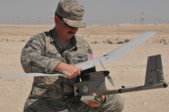 Senior Airman James McGaha, 379th Expeditionary Security Force Squadron patrolman, recovers parts of the Raven B Digital Data Link drone Feb. 19, 2016, at Al Udeid Air Base, Qatar. After completing its flight, the Raven's wings detached after landing which can occur and is easy to fix. (U.S. Air Force photo/Tech. Sgt. Terrica Y. Jones)