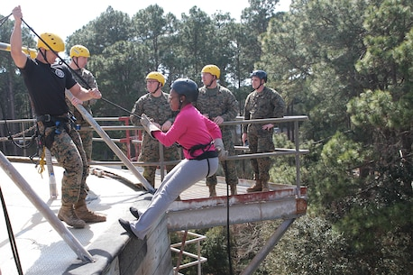 An educator leans back into their harness to begin their scale down a fifty foot rappel tower March 3, 2016, about Marine Corps Recruit Depot Parris Island, S.C. The rappel tower is a part of the Marine recruit experience to earn the title Marine. Educators from Recruiting Stations Atlanta and Columbia have embarked on a three-day workshop to learn more about the Marine Corps so when their students inquire about the military they are well informed. (Official Marine Corps photo by Cpl. Diamond N. Peden/Released)