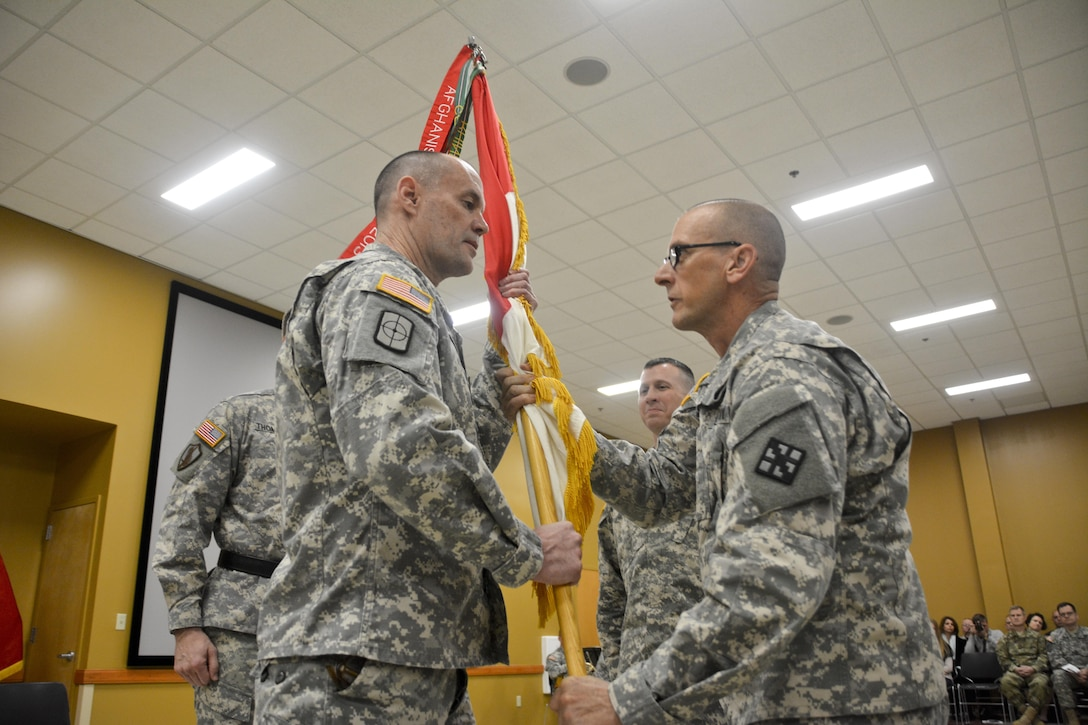 U.S. Army Reserve Command Sgt. Maj. Michael Boyd (right), senior enlisted adviser, 411th Engineer Brigade, passes the brigade colors to Col. Ralph Henning, outgoing commander, 411th Engineer Brigade, during the change of command ceremony March 5 in New Windsor, N.Y. (U.S. Army photo by Nathan Fanton)