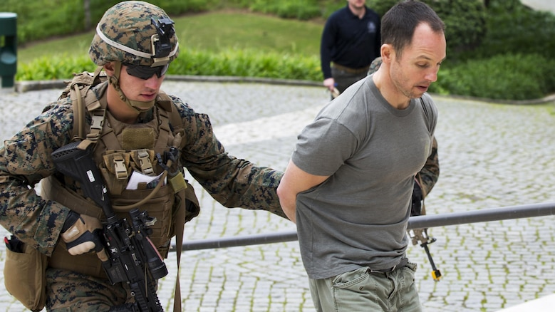 U.S. Marine Corps Lance Cpl. Noah S. Scalish, (left), automatic rifleman, 2nd platoon Bravo Company, 1st Battalion, 8th Marine Regiment, Special-Purpose Marine Air-Ground Task Force-Crisis Response-Africa escorts a simulated suspect during an active shooter exercise at U.S. Embassy, Lisbon, Portugal, Feb. 9, 2016. SPMAGTF-CR-AF conducts a scaled embassy reinforcement exercise at American Embassy Lisbon in coordination with the Regional Security Office and host nation security forces in order to enhance mission essential  task proficiency and build relationships.