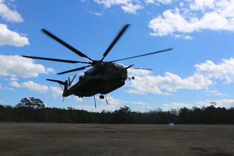 A CH-53E Super Stallion prepares to pick up its intended cargo during a helicopter support team exercise, aided by Marines with Landing Support Platoon, Combat Logistics Battalion 2 at Camp Lejeune, N.C., March 2, 2016. The training allows squadron pilots to practice loading and unloading cargo from a CH-53 Super Stallion without touching the ground, as well as allow the Marines with CLB-2 to sharpen their reaction times while helping load and unload cargo. The Marines working underneath the Super Stallion all have critical roles in ensuring mission accomplishment, working together to attach the equipment on the ground  to the helicopter while it hovers in the air about 10 feet above them. (Marine Corps photo by Cpl. Shannon Kroening)