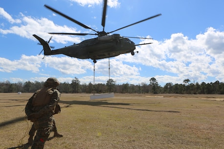 A CH-53E Super Stallion lifts cargo during a helicopter support training exercise, aided by Marines with Landing Support Platoon, Combat Logistics Battalion 2 aboard Camp Lejeune, N.C., March 2, 2016.  Helicopter support team missions are critical to mission accomplishment because they provide the ability to quickly and efficiently provide support to other Marines on the ground, and they assist with the loading and unloading of important equipment such as small vehicles, supplies, and food rations in a moment's notice. (Marine Corps photo by Cpl. Shannon Kroening)