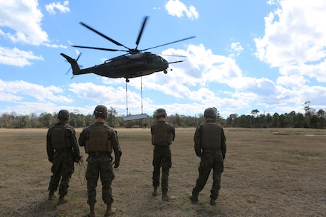 Marines with CLB-2 wait for the command to rush the cargo after it has been dropped by a CH-53E Super Stallion during a helicopter support team exercise aboard Camp Lejeune, N.C., March 2, 2016. The Marines working underneath the Super Stallion have critical roles in ensuring mission accomplishment, working together to attach the equipment on the ground  to the helicopter while it hovers in the air about 10 feet above them. The training allows squadron pilots to practice loading and unloading cargo from a CH-53 Super Stallion without touching the ground, as well as allow the Marines with CLB-2 to sharpen their reaction times while helping load and unload the cargo. (Marine Corps photo by Cpl. Shannon Kroening)