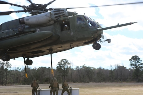 Marines with CLB-2 prepare to attach cargo to a CH-53E Super Stallion during a helicopter support team exercise aboard Camp Lejeune, N.C., March 2, 2016. The Marines working underneath the Super Stallion have critical roles in ensuring mission accomplishment, working together to attach the equipment on the ground  to the helicopter while it hovers in the air about 10 feet above them.  The training allows squadron pilots to practice loading and unloading cargo from a CH-53 Super Stallion without touching the ground, as well as allow the Marines with CLB-2 to sharpen their reaction times while helping load and unload the given cargo. (Marine Corps photo by Cpl. Shannon Kroening