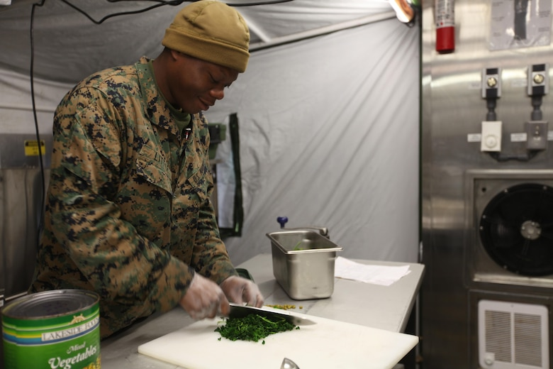 Cpl. Tyrone Little chops cilantro in a field expedient kitchen at Marine Corps Air Station Cherry Point, N.C., Jan. 20, 2016. Food service specialists with Marine Wing Support Squadron 274 compete for the Maj. Gen. William Pendleton Thompson Hill Food Service Award. In a field-like environment, the Marines set up a field expedient kitchen and cooked various entrées in hopes of winning the title of Best Field Mess Award. The Marines were inspected on sanitation, preparation and meal production. Little is a food service specialist with MWSS-274. (U.S. Marine Corps photo by Cpl. Unique Roberts/ Released)