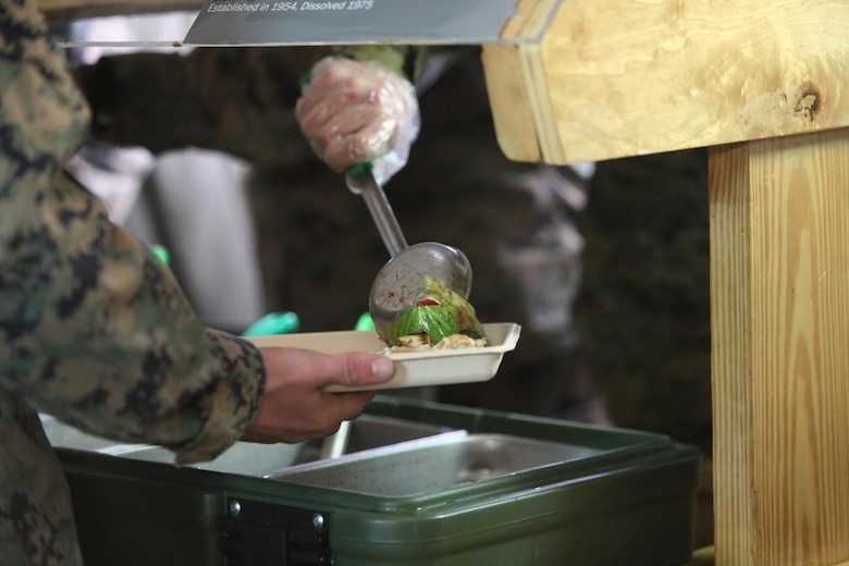 Food service specialists serve food to Marines at Marine Corps Air Station Cherry Point, N.C., Jan. 20, 2016. Marines with Marine Wing Support Squadron 274 cooked various dishes in a field-like environment to compete in the Maj. Gen. William Pendleton Thompson Hill Food Service Award competition. The Marines prepared dishes like shrimp and ham jambalaya, onion scallion beef and Vietnamese chicken noodle soup. In addition to being critiqued on the production of the food, the Marines were critiqued on sanitation and preparation. (U.S. Marine Corps photo by Cpl. Unique Roberts/ Released)