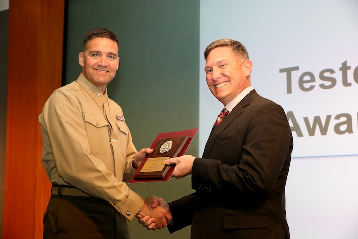 Timothy D. McLean (right), a senior technical advisor within the Marine Corps Tactical Systems Support Activity Test and Certification Group, receives the National Defense Industrial Association 2016 Tester of the Year Award from Col. Benjamin Stinson, commanding officer of MCTSSA. The award is presented to outstanding individuals in the field of Test and Evaluation. (U.S. Marine Corps photo by Emily Greene)