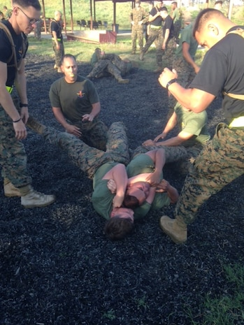 Sergeant's McGrortyHunter and Brooks supervise a rear naked choke applied on Corporal Ramrui of 1st TSB Corporals Course  349-16 ensuring proper technique and tap out procedures are applied during the training evolution.