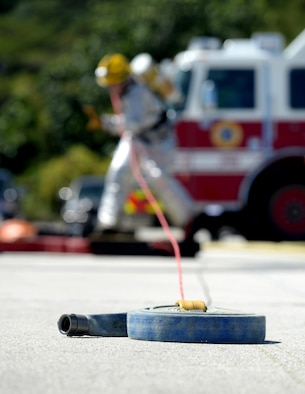 Staff Sgt. Anthony Whitney, 36th Civil Engineer Squadron fire protection crew chief, pulls a fire hose during the annual Guam Fire Muster competition March 5, 2016, in Hagåtña, Guam. The competition included firefighting teams from the Guam Airport Fire Rescue, Guam Fire Department, Naval Base Guam Fire Department, Saipan Airport aircraft rescue and Andersen Air Force Base. (U.S. Air Force photo/Staff Sgt. Benjamin Gonsier)