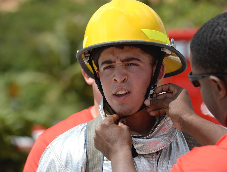 Airman 1st Class Jared May, 36th Civil Engineer Squadron fire protection crew chief, has his helmet fastened to his head during the annual Guam Fire Muster competition March 5, 2016, in Hagåtña, Guam. The fire muster tests a firefighter's ability to perform basic firefighting techniques to include spraying a target with water, navigating through obstacles, carrying a casualty and using a sledgehammer. (U.S. Air Force photo/Staff Sgt. Benjamin Gonsier)