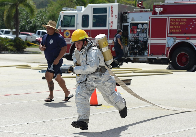 Airman 1st Class Jared May, 36th Civil Engineer Squadron fire protection crew chief, sprints with a hose during the annual Guam Fire Muster competition March 5, 2016, in Hagåtña, Guam. The fire muster tests a firefighter's ability to perform basic firefighting techniques to include spraying a target with water, navigating through obstacles, carrying a casualty and using a sledgehammer. (U.S. Air Force photo/Staff Sgt. Benjamin Gonsier)