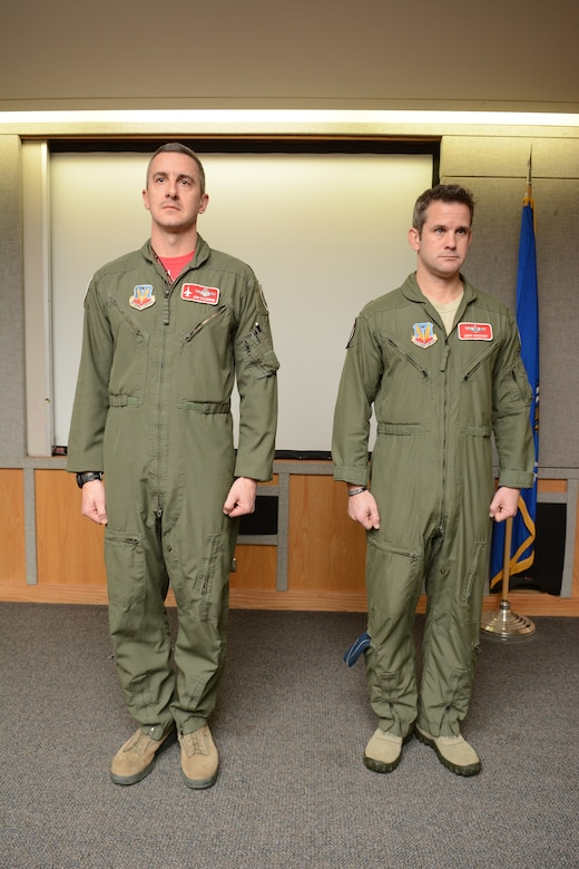 Maj. Adam Kinzinger, 115th Fighter Wing RC-26 Metroliner pilot, stands beside Col. Jon Kalberer, 176th Fighter Squadron commander, as The Meritorious Service Medal award package is read during a ceremony at Truax Field, Madison, Wis., March 5, 2016. Kinzinger received the award for various mission accomplishments including 420 million dollars of drug-related seizures, more than 700 arrests of high-value drug traffickers, and two deployments in support of overseas contingency operations where he executed over 275 combat flight hours and 100 combat sorties. (U.S. Air National Guard photo by Staff Sgt. Andrea F. Rhode)