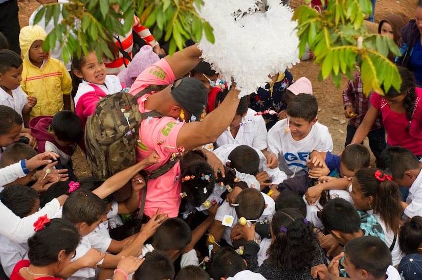 A member of Joint Task Force-Bravo helps open a piñata during Chapel Hike 66 at Tierra Colorada, March 5, 2016. During the regularly occurring hikes, service members and civilians from Soto Cano Air Base hike to villages local leaders identify as most in need of the goods the volunteers bring with them. (U.S. Air Force photo by Capt. Christopher Mesnard)