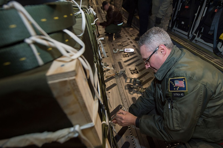 Air Force Senior Master Sgt. Jeffrey Watson, 249th Airlift Squadron senior enlisted manager, prepares to set up a release gate before taking off at Joint Base Elmendorf-Richardson, Alaska, March 2, 2016. (U.S. Air Force photo by Staff Sgt. Sheila deVera)